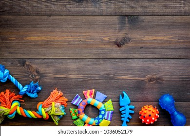 Toys for pets dog and cat. Rubber and textile accessories on dark wooden background top view copy space