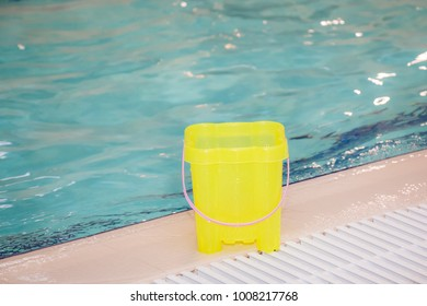 Toys for playing in the swimming pool, yellow plastic bucket for children. Close up. Copy space.