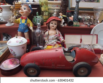 Toys for sale at the flea market: Pinocchio, a doll and an old little car.