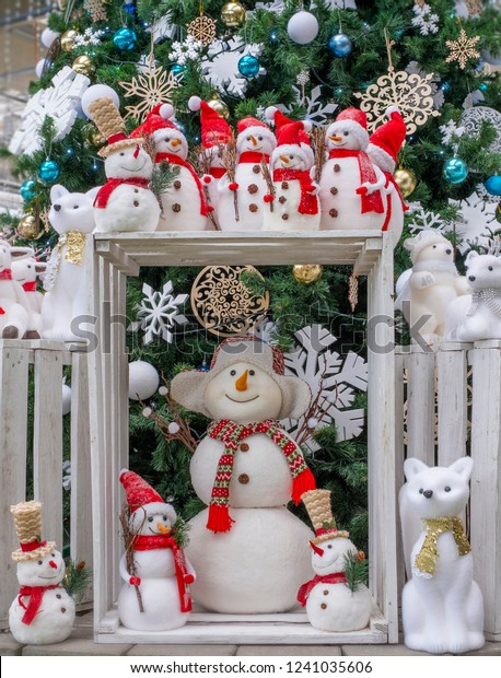 A lot of toys snowmen, deer, bears and fox, standing under the tree, Christmas toys
