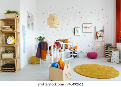 Toys in wooden box next to yellow carpet in scandi baby's room with clock on shelf and white cradle