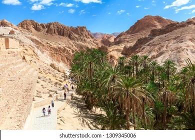 TOZEUR, TUNISIA-CIRCA MAY, 2012: Visitors walk in Chebika (Qasr el-Shams) mountain oasis at foot of the Djebel el Negueb in western Tunisia. It is famous tourist place and backstage of Star Wars movie