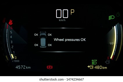 TPMS (Tyre Pressure Monitoring System) monitoring display on car dashboard panel. Checking tires pressures. Car instrument panel with speedometer, tachometer, odometer, fuel gauge, seatbelt reminder.
