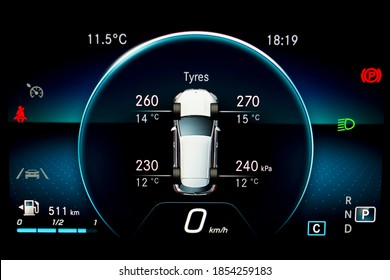 TPMS (Tyre Pressure Monitoring System) with temperature measurement monitoring display on car dashboard panel. Checking tires pressures and temperature. Car cluster with speedometer and fuel gauge.