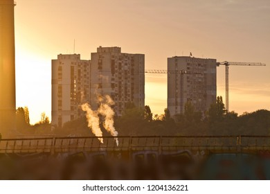 TPP thermal power plant on a sunrise. Refinery with smokestacks. Smoke from factory pollutes the environment. High red and white tower of CHPP. TPP produce steam for electric power. Pollution, climate