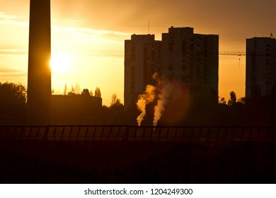 TPP thermal power plant on a sunrise. Refinery with smokestacks. Smoke from factory pollutes the environment. photo against sun, no distraction elements
