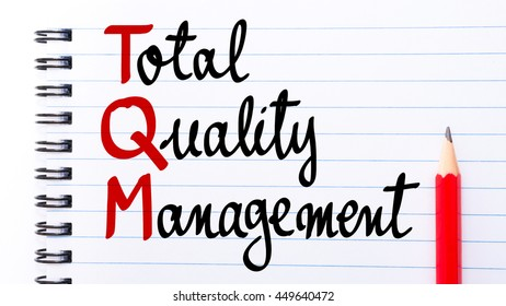 TQM Total Quality Management written on notebook page with red pencil on the right