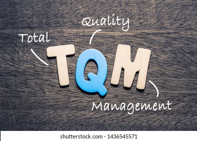 TQM wooden alphabets on wood background with text acronym (Total Quality Management)