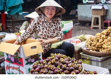 TRA VINH, VIETNAM - APR 06: Unidentified woman with smile sells fruits in a local market, on April 06, 2013, in Tra Vinh province, Vietnam.