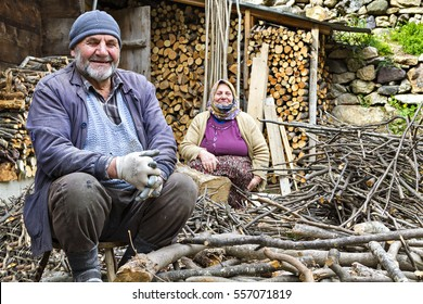 TRABZON, TURKEY - APRIL 2, 2014: Elderly Turkish couple smile and look at me while chopping the fire wood in Trabzon, Turkey.