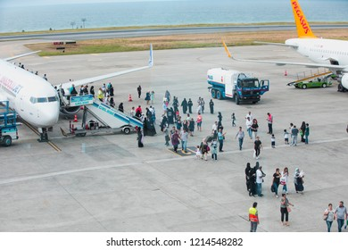 TRABZON, TURKEY - JULY 15, 2018: Traveler Arab tourists get off the plane with suitcase in the Trabzon Airport -  Passengers getting on airplane of Anadolu Jet airlines