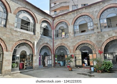 Trabzon, Turkey - September 8, 2018. Courtyard of historic Tas Han, commercial building dating from 1530, in Trabzon, with commercial properties and people.