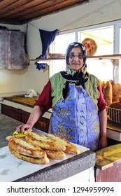 TRABZON, TURKEY-AUG. 4, 2011:  In a tiny village in the hills near Trabzon a Turkish woman sells bread she has baked in her bakery.