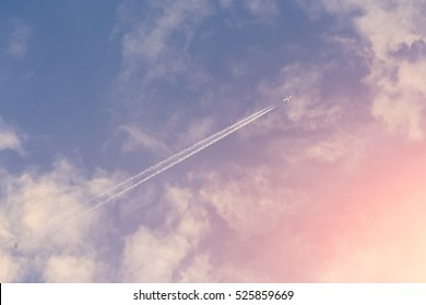 Trace from an airplane against blue sky with pink clouds