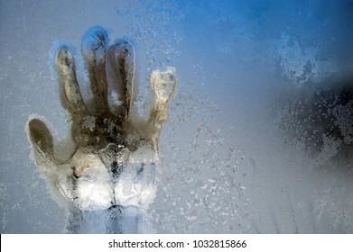 A trace of a hand on a frozen winter window