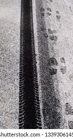 traces of human shoes on a snowy road and next to a tire imprint from the wheel of a car