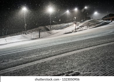 Traces of ratrak on prepared track, specially for skiing and snowboarding in the mountains of winter resort. Heavy snowfall at night