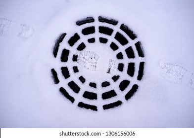 Traces of shoes are on the snow-covered road and a metal cap wastewater that looks like a spider web. Close-up.