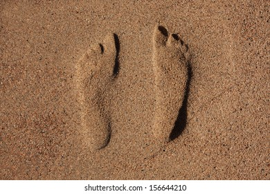 Traces of two human feet in the sand