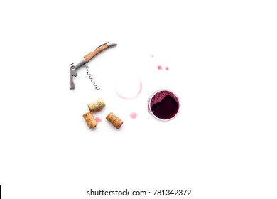 Traces of wine near corkscrew and glass of beverage on white background top view copyspace