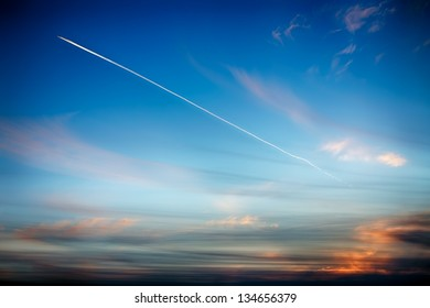 Track aircraft in the sky against the background of a beautiful sunset