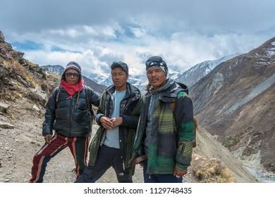 Track around Annapurna, Nepal-06.04.2018: three young Nepalese on the mountain trail 6 April 2018 on the track around Annapurna, Nepal.
