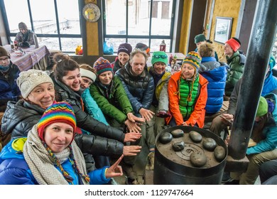 Track around Annapurna, Nepal-06.04.2018: Tourists bask at the stove in the cabins of the base camp at the pass Thorong La on April 6, 2018 on the track around Annapurna, Nepal.