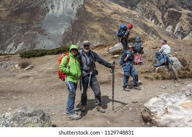 Track around Annapurna, Nepal-06.04.2018: Tourists relax on the mountain trail 6 April 2018 on the track around Annapurna, Nepal.