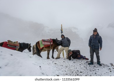 Track around Annapurna, Nepal-07.04.2018: People and horses on the snowy Thorong La pass April 7, 2018 on the track around Annapurna, Nepal.