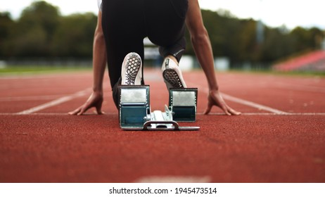 Track and Field Athlete being ready in the blocks alone with no competition, sprinter, empty lanes, lonely, training, practise, spikes