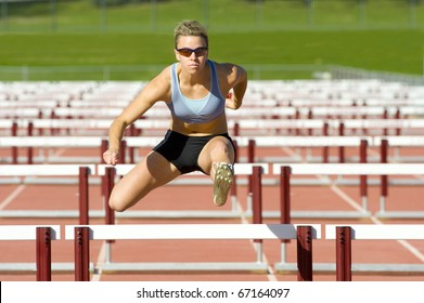 Track and field athlete jumps over hurdles.
