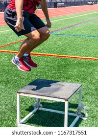 A track and field athlete perfoming plyometric box jumps outside on a green turf field.