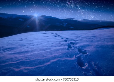 The track of footprints on a fresh snow in a carpathian mountain valley. Majestic milky way in a night sky. Ukraine, Europe
