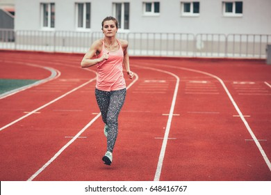 Track runner athlete woman warming up before running at a stadium