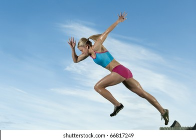 Track runner bursts off starting block against a blue sky.