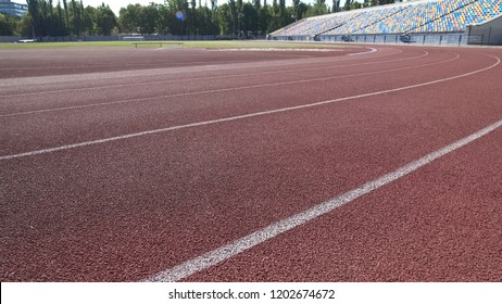 Track for runners at stadium, empty seats in background, sports training program