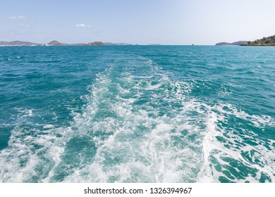 Track trail behind of speed boat on sea surface with clear sky in background.