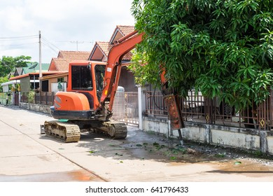 Tracked excavator is digging cement street in the village for fixing water pipe