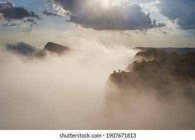 Tracker stands on the top of a mountain in the light of the sun and clouds.