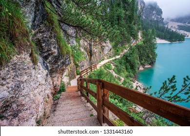 Tracking and walking route with wooden fence around fantastic lake Braies (Lago di Braies). Lake is surrounded by mountains. 1st point of trekking route Alta Via 1, Dolomites Alps, South Tyrol, Italy