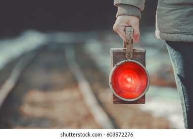 A trackman on the railway signals a red lantern