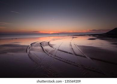 Tracks on the sand on cromer beach at sunrise
