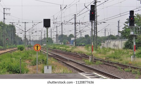 Tracks of a railway / railroad with a red signal and a sign forbidden entry on a cloudy day in Germany. (Railway station of Emmerich)