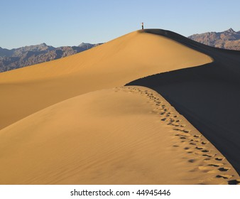 Tracks in sand dune leading to lone person standing with arms raised. Horizontal shot.