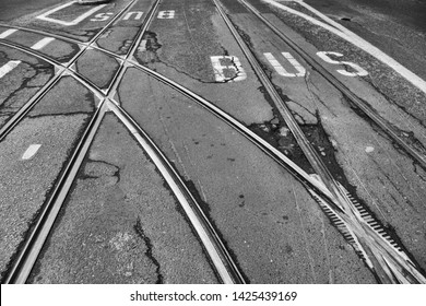 Tracks of tram with script of bus line at desolate Asphalt road in black and white
