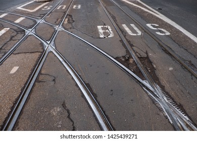 Tracks of tram with script of bus line at desolate Asphalt road