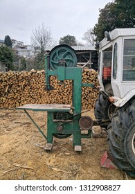 Tracktor with bandsaw attached with firewood in background