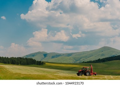 Tracktor collecting hay in mountain meadow at springtime