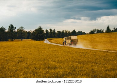 Tracktor driving on a dirt road in the middle of a wheat field