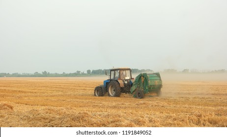 Tracktor on a yellow field. Tracktor collecting hay in meadow at autumn.